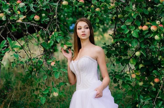 Retrato de uma noiva linda em um vestido de noiva andando e sozinha no jardim de maçãs
