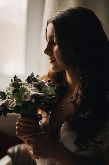 Retrato de uma noiva linda menina morena com um buquê