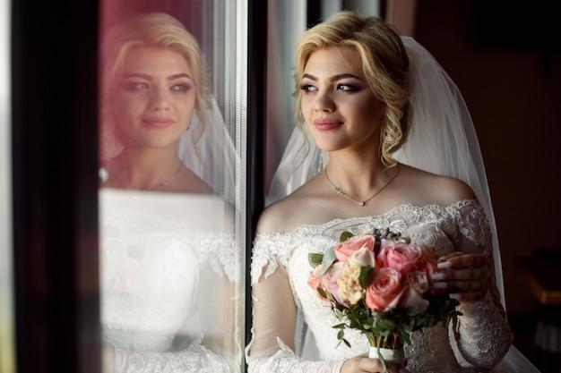 Retrato de uma noiva loira com um buquê de rosas cor de rosa interior. . jovem noiva sorridente com um lindo decote em vestido de luxo perto da janela. dia do casamento.