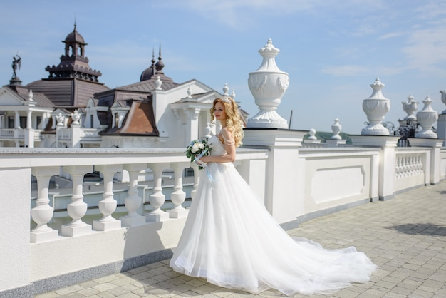 Retrato de uma noiva loira linda com um buquê.