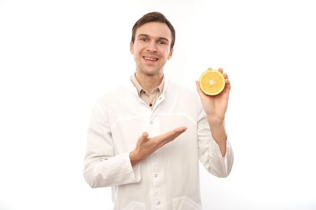 Retrato de uma nutricionista médica sorridente positiva com laranjas.