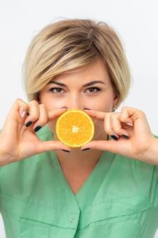 Retrato de uma nutricionista segurando e mostrando uma fatia de laranja contra os lábios em uma parede branca