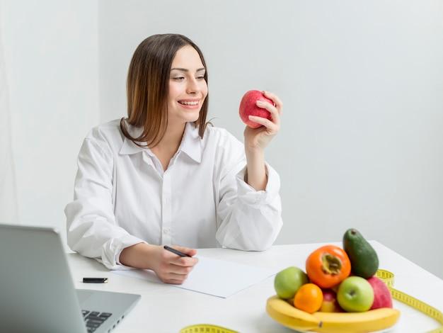 Retrato de uma nutricionista sentada à mesa com frutas.