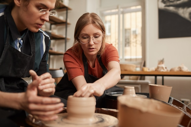 Retrato de uma oleira ajudando jovem a dar forma a argila na roda de oleiro na oficina, copie o espaço