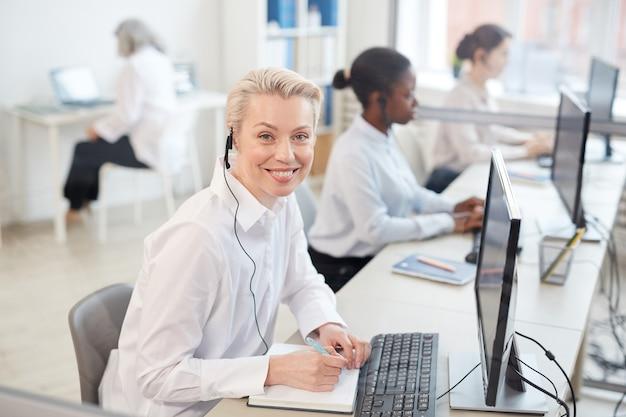 Retrato de uma operadora usando um fone de ouvido e sorrindo enquanto está sentada na fila no call center ou no interior do escritório