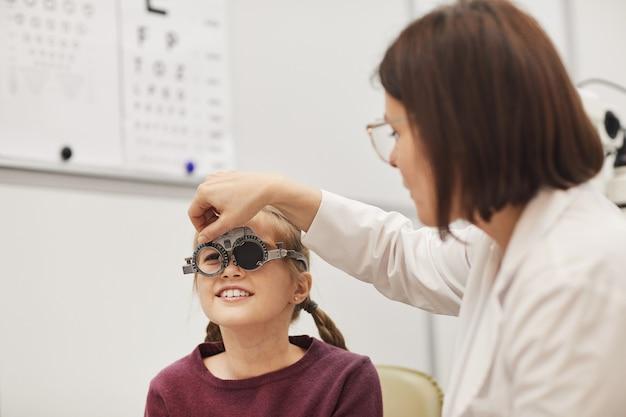 Retrato de uma optometrista configurando a estrutura de teste enquanto verifica a visão da menina