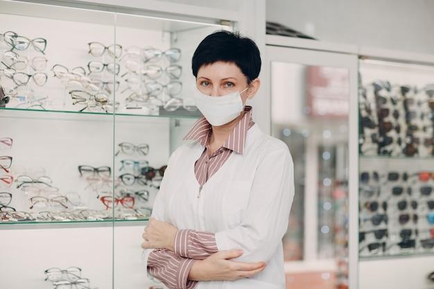 Retrato de uma optometrista oftalmologista, mulher de meia-idade usando máscara protetora médica
