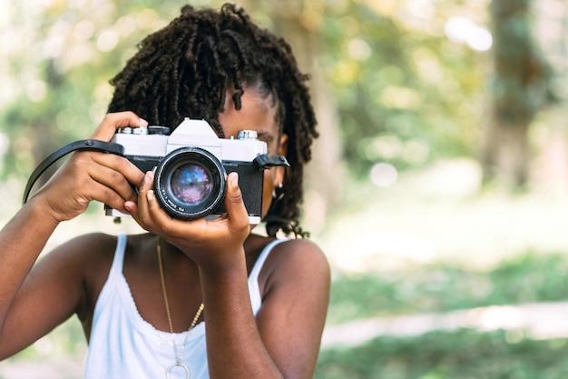 Retrato de uma pequena jovem africana segurando uma câmera e tirando uma foto divertida e conceito de infância