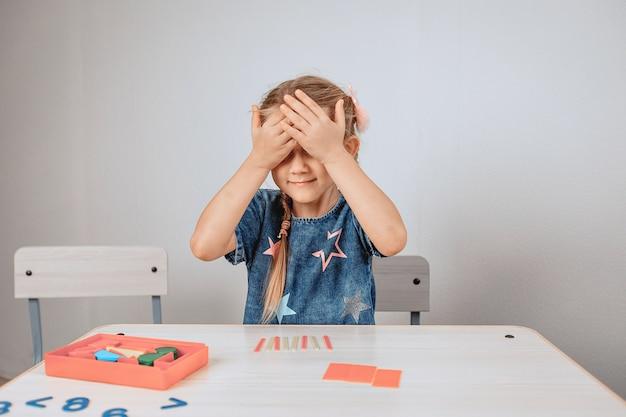 Retrato de uma pequena jovem bonita e fofa sentada à mesa rodeada por um grande número de quebra-cabeças e fechando os olhos de excitação. conceito de desenvolvimento. foto com ruído
