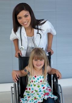 Retrato de uma pequena menina em uma cadeira de rodas e um jovem médico