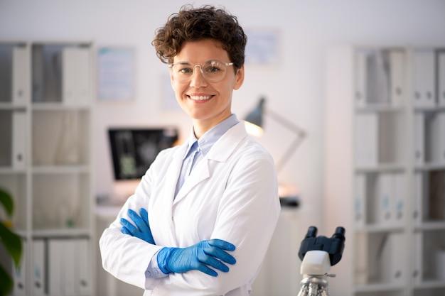 Retrato de uma pesquisadora de laboratório, mulher confiante e positiva, de óculos e jaleco branco, de braços cruzados