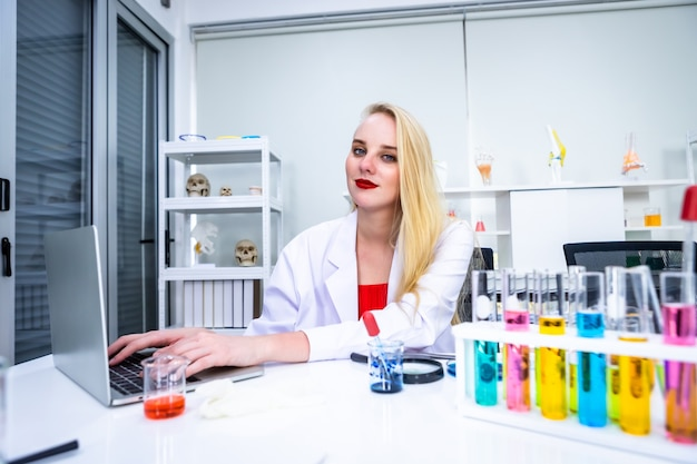 Retrato de uma pesquisadora trabalhando com um computador laptop e uma pesquisa em um cientista de laboratório de química segurando um tubo de ensaio com uma amostra no fundo de análise de laboratório