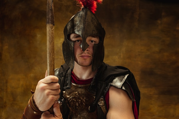 Retrato de uma pessoa medieval, guerreiro em equipamento de guerra isolado em fundo escuro vintage.