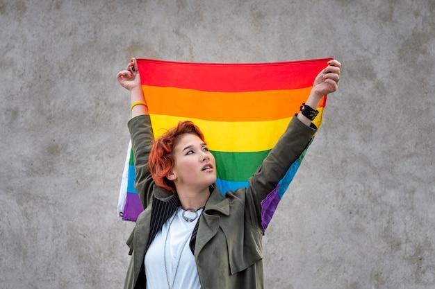 Retrato de uma pessoa não binária ruiva segurando uma bandeira lgbt