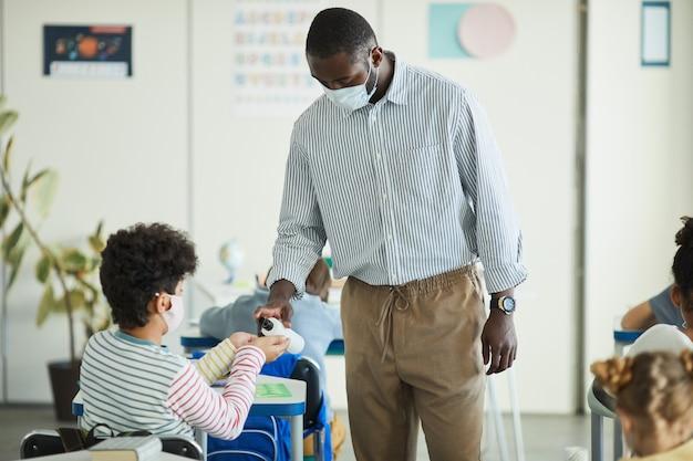 Retrato de uma professora afro-americana higienizando as mãos de crianças na sala de aula, medidas de segurança ambiciosas, copie o espaço