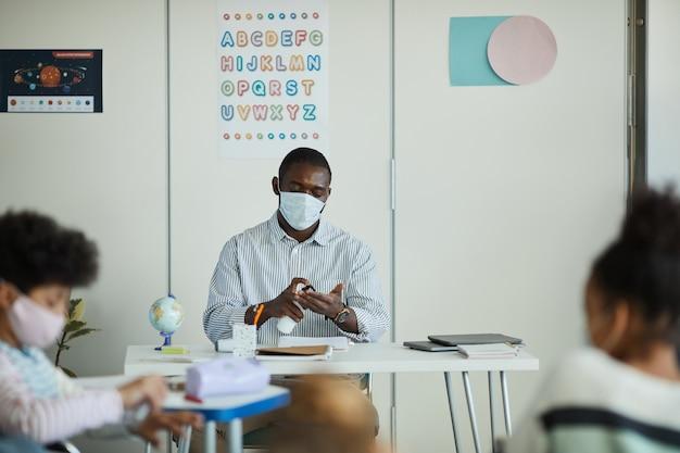 Retrato de uma professora afro-americana higienizando as mãos na sala de aula, medidas de segurança ambiciosas, copie o espaço