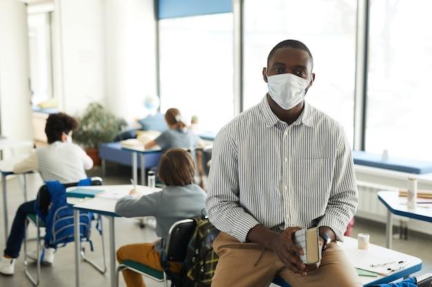 Retrato de uma professora afro-americana usando máscara na sala de aula da escola e olhando para a câmera, copie o espaço