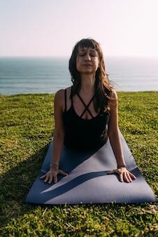 Retrato de uma professora de ioga esticando o corpo fora de casa. copie o espaço