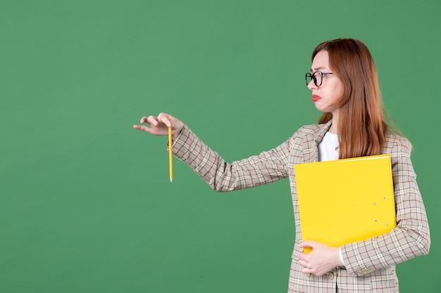 Retrato de uma professora segurando um documento amarelo e olhando de lado no verde