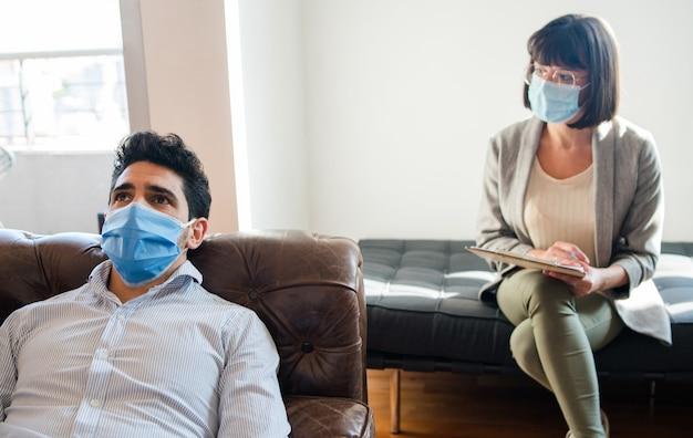 Retrato de uma psicóloga conversando com seu paciente e fazendo anotações enquanto ele está deitado no sofá durante uma sessão de terapia