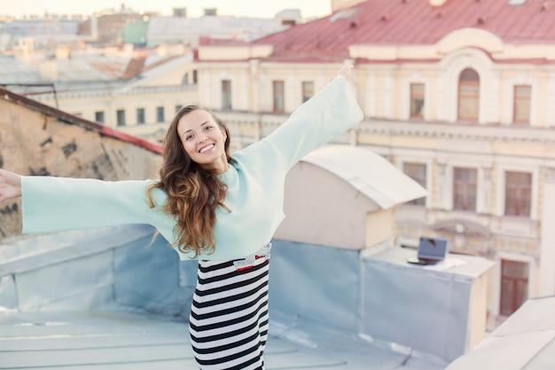 Retrato de uma rapariga bonita nos telhados.