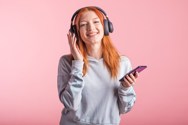 Retrato de uma ruiva alegre que ouve música em fones de ouvido com seu smartphone no estúdio em um fundo rosa