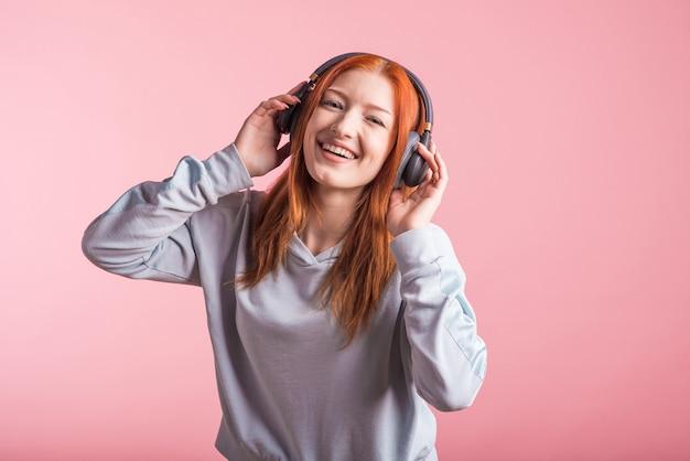 Retrato de uma ruiva alegre que ouve música em fones de ouvido no estúdio em um fundo rosa