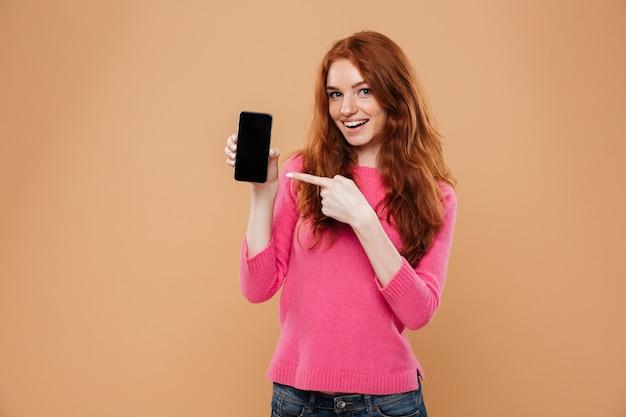 Retrato de uma ruiva atraente animado, apontando para o smartphone
