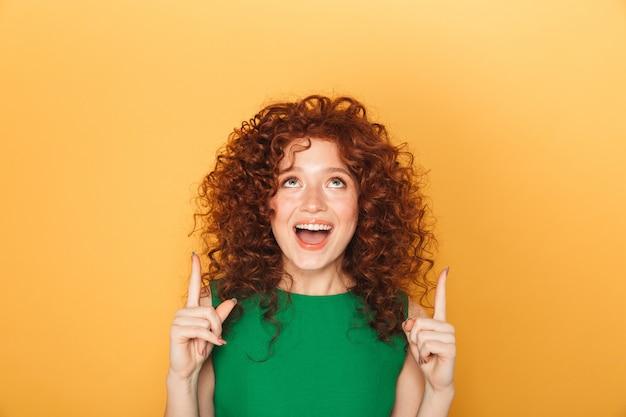 Retrato de uma ruiva cacheada animada apontando os dedos para cima