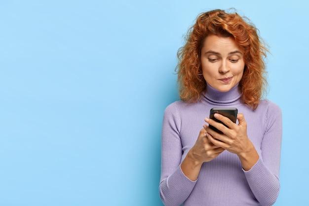 Retrato de uma ruiva de aparência agradável focada em um smartphone, verifica a caixa de e-mail, bate-papo online