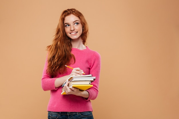 Retrato de uma ruiva feliz e pensativa segurando livros
