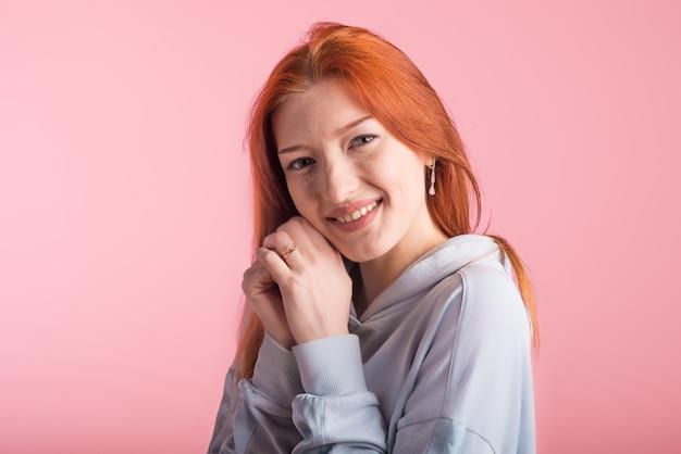 Retrato de uma ruiva feliz no estúdio em um fundo rosa