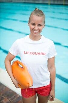 Retrato de uma salva-vidas segurando uma lata de resgate à beira da piscina