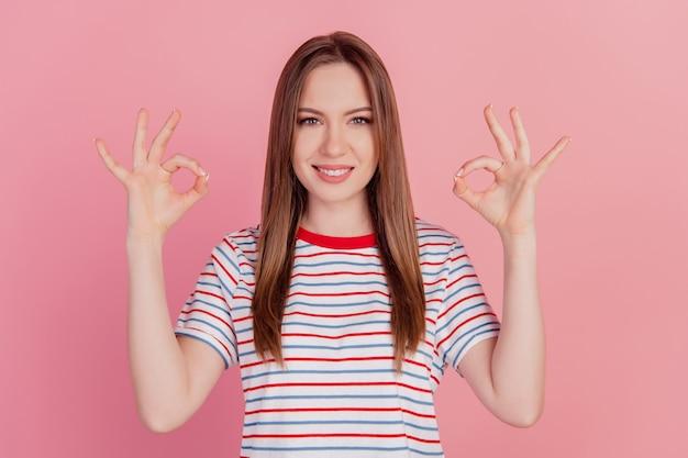 Retrato de uma senhora alegre e confiável com dedos mostrando sinal de bom sorriso dentuço no fundo rosa