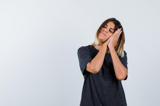 Retrato de uma senhora apoiada nas palmas das mãos como travesseiro em uma camiseta preta e com uma vista frontal tranquila