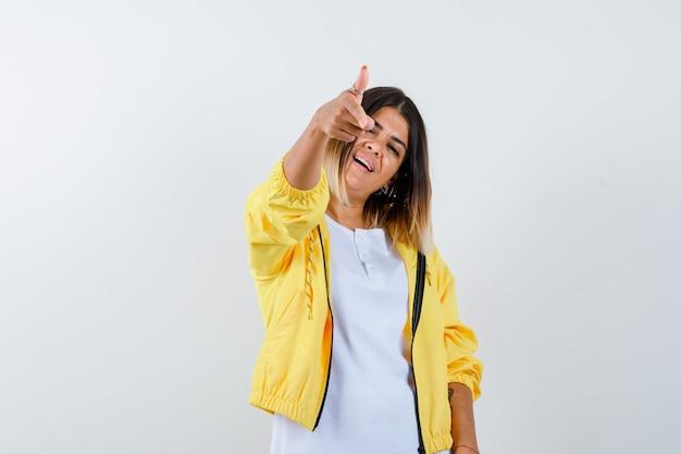 Retrato de uma senhora apontando para a câmera com uma camiseta, jaqueta e uma visão frontal confiante