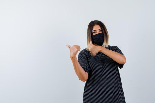 Retrato de uma senhora apontando para a esquerda com polegares em um vestido preto, máscara médica e olhando confiante para a frente