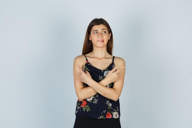 Retrato de uma senhora atraente apontando para cima e mordendo o lábio inferior na blusa, com uma vista frontal preocupada