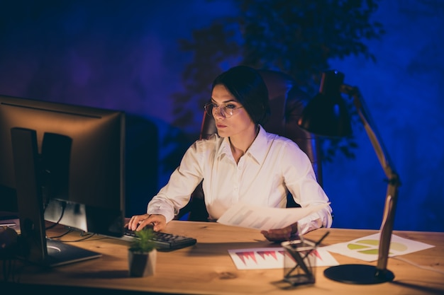 Retrato de uma senhora atraente, atraente e habilidosa, gerente executivo de marketing ceo chefe, chefe, calculando, analisando o progresso da taxa de investimento, resultado comercial, prazo da conta à noite, escuro estação de trabalho