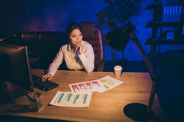Retrato de uma senhora atraente, elegante, elegante, focada, gerente executivo, empresa de finanças, proprietário da agência, criando uma nova estratégia de inicialização, relação de investimento depósito p à noite escura estação de trabalho