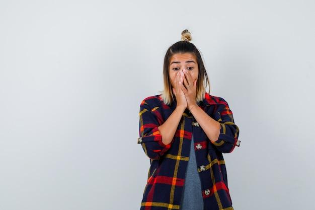 Retrato de uma senhora bonita com as mãos no rosto em uma camisa casual e olhando de frente para o ar espantado