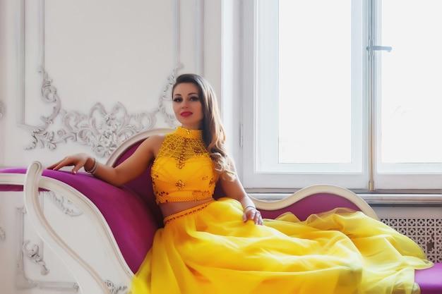 Retrato de uma senhora bonita em um vestido amarelo longo estágio no sofá roxo perto da janela, sessão de fotos elegante, cor criativa. modelo de jovem no interior da sala de estúdio. cartaz para publicidade. copie o espaço