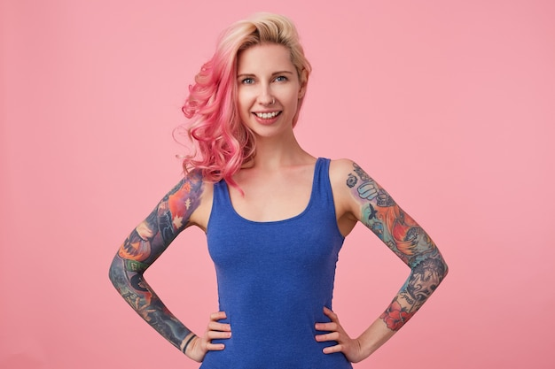 Retrato de uma senhora bonita feliz com cabelo rosa e mãos tatuadas, em pé e sorrindo amplamente, vestindo uma camisa azul. conceito de pessoas e emoção.