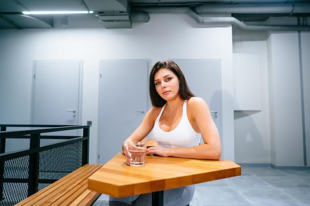 Retrato de uma senhora bonita no topo desportivo com copo de água