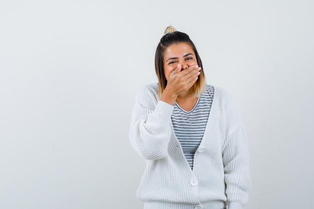 Retrato de uma senhora bonita segurando a mão na boca em uma camiseta, casaco de lã e parecendo feliz