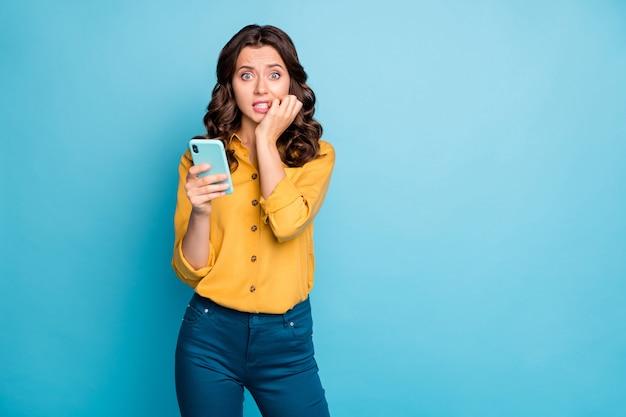 Retrato de uma senhora bonita segurando as mãos do telefone, mordendo os dedos, olhos cheios de medo, comentários negativos postar calças de camisa amarela.