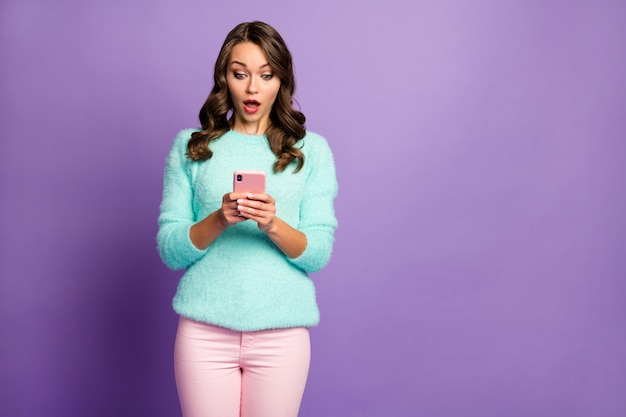 Retrato de uma senhora bonita sem palavras segurar as mãos do telefone ler os comentários negativos do blogue da postagem usar calças casuais de suéter cor-de-rosa fofo fuzzy menta pastel.