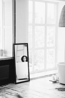 Retrato de uma senhora bonita, tendo um banho de leite vista do espelho