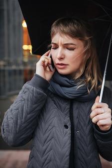 Retrato de uma senhora chateada em pé na rua com um guarda-chuva preto e falando ao celular
