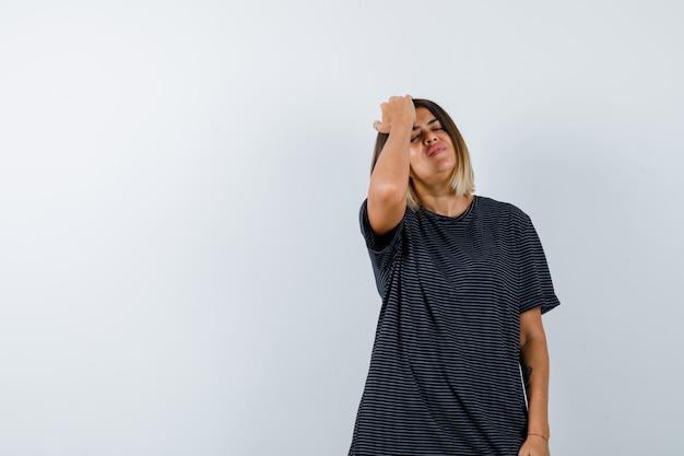 Retrato de uma senhora com a mão na cabeça em uma camiseta preta e parecendo relaxada vista frontal
